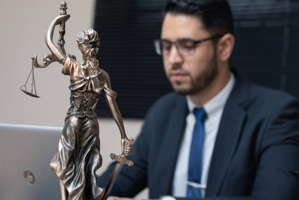 LAwyer sitting at the table with the Lady Justice statue next to him. Workers Compensation Lawyers.