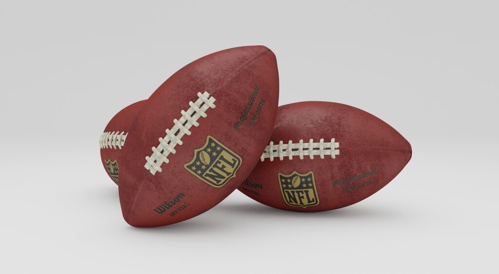 2 football balls next to each other. What does the NFL & JLO have in common?