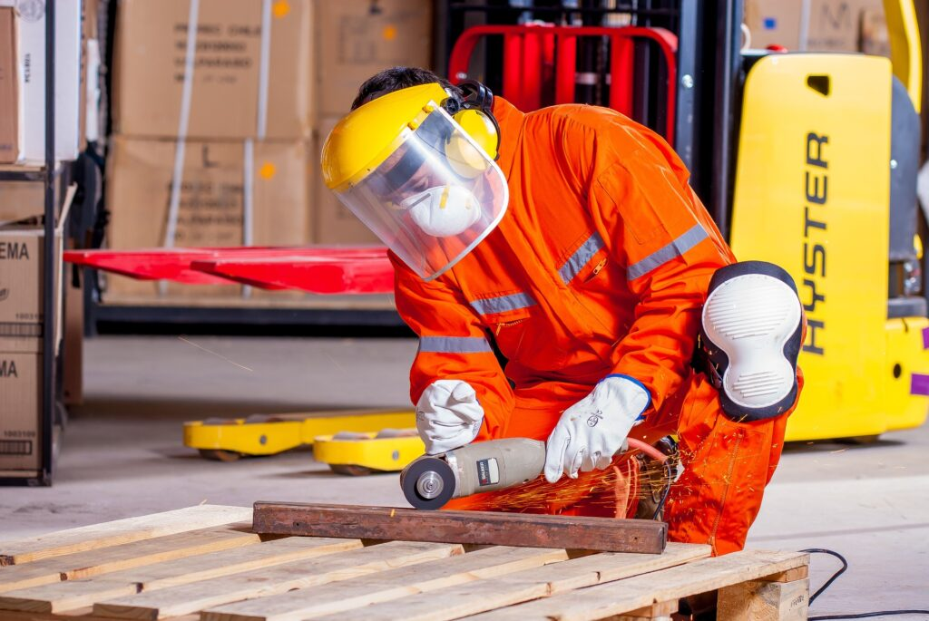 Hearing Protection At Work. Man cutting metal in protective gear on work.