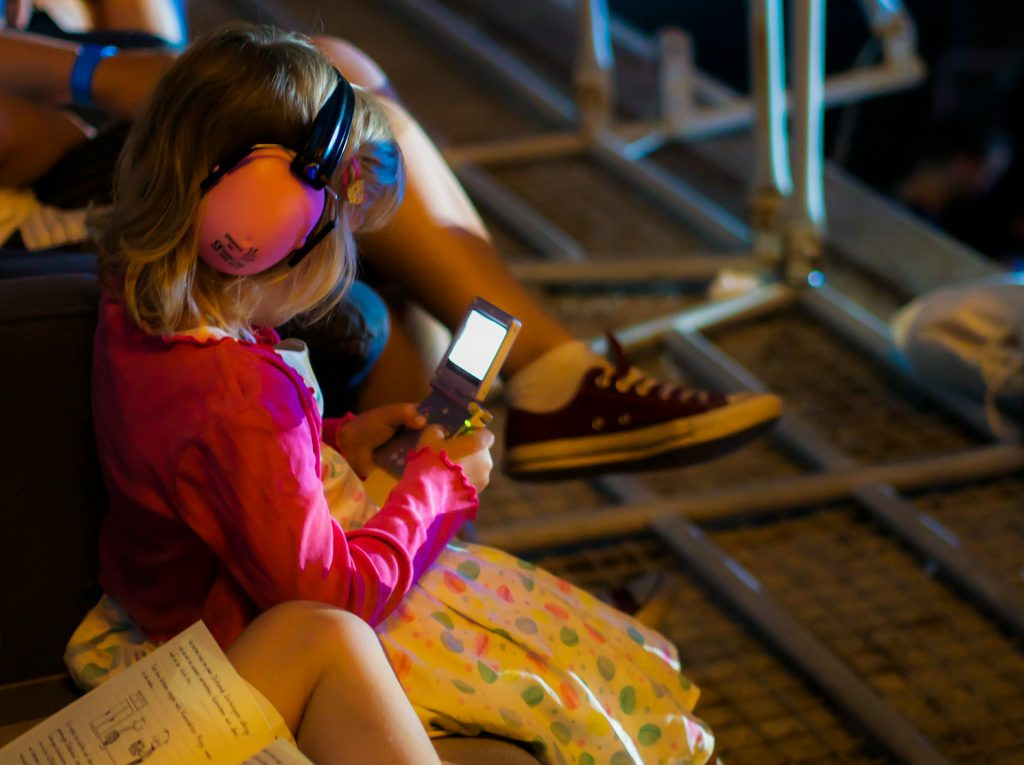 Little girl with ear muffs looking at the phone. Types of Hearing Protection