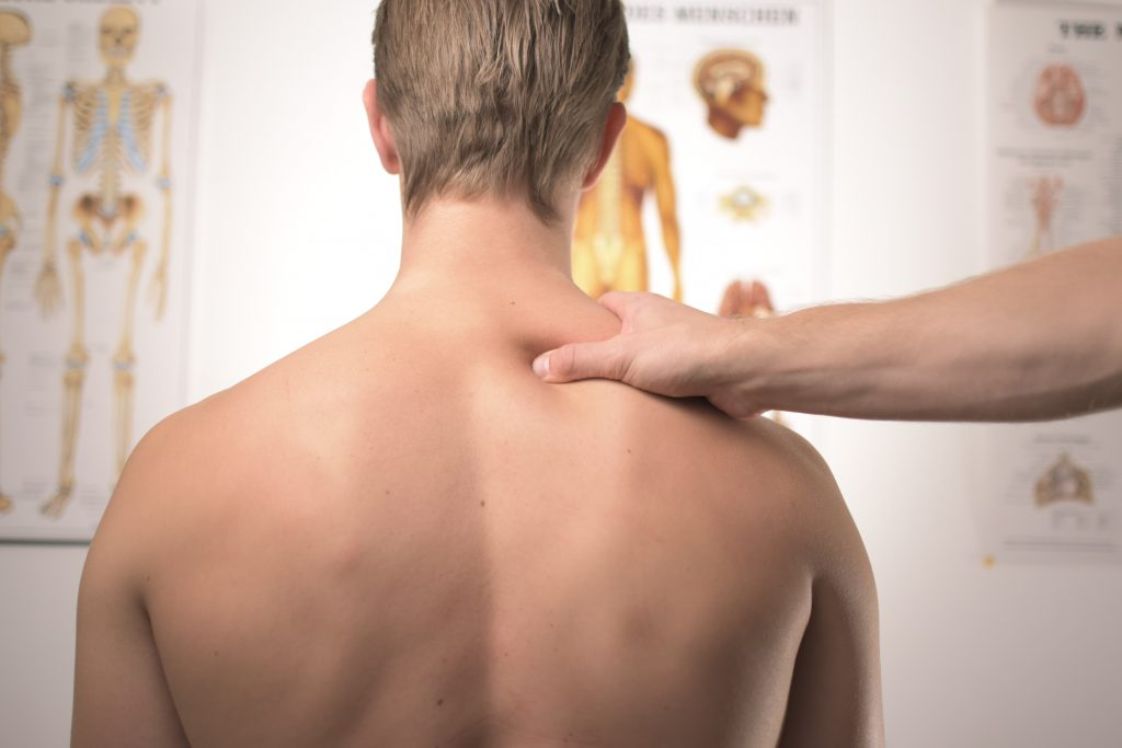 Man on medical examination with doctor checking his back