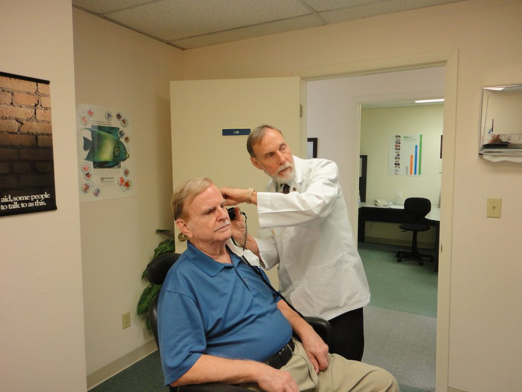 What to expect at the audiologist? Man going throug a hearing check with doctor examining him