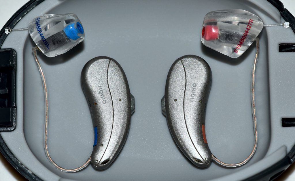 Hearing aid devices on the gray background. which brand of hearing aid is the best?