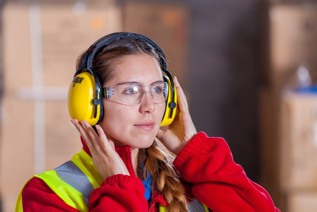 Woman with hearing protection headphones and googles at work.