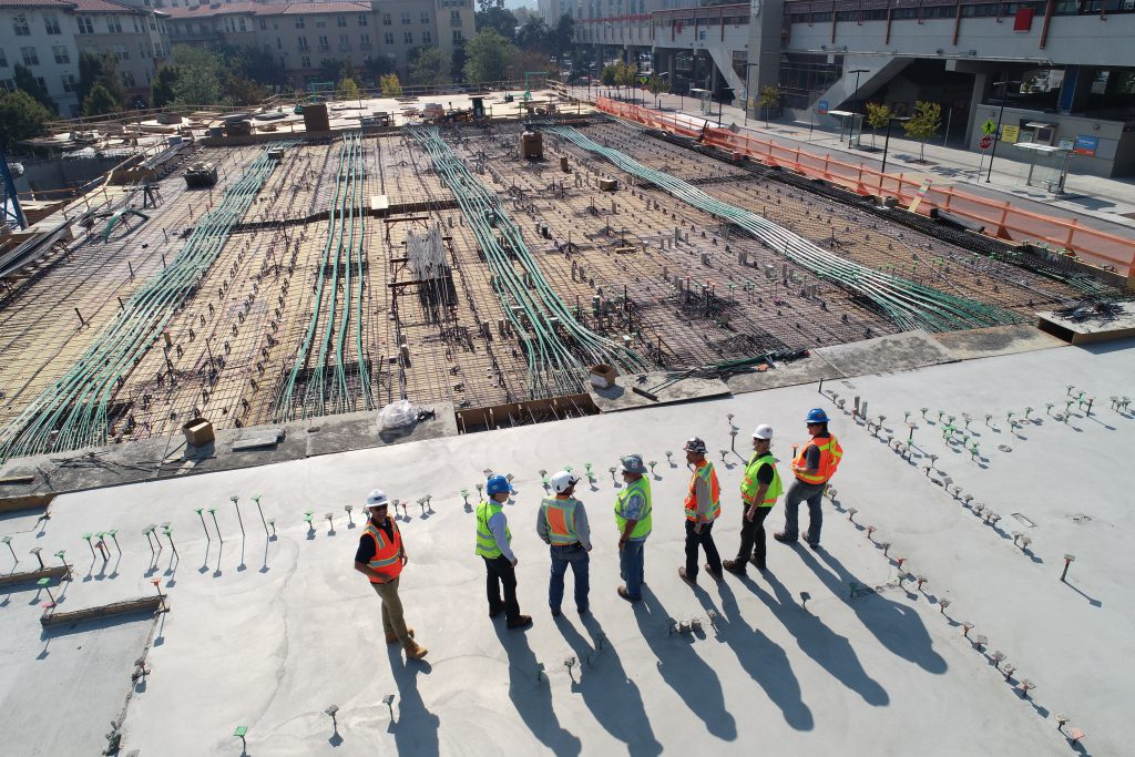 Seven workers standing on the newly built building watchg at the construction site.