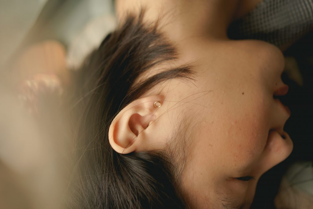 Woman lying on her side with a focus on the ear