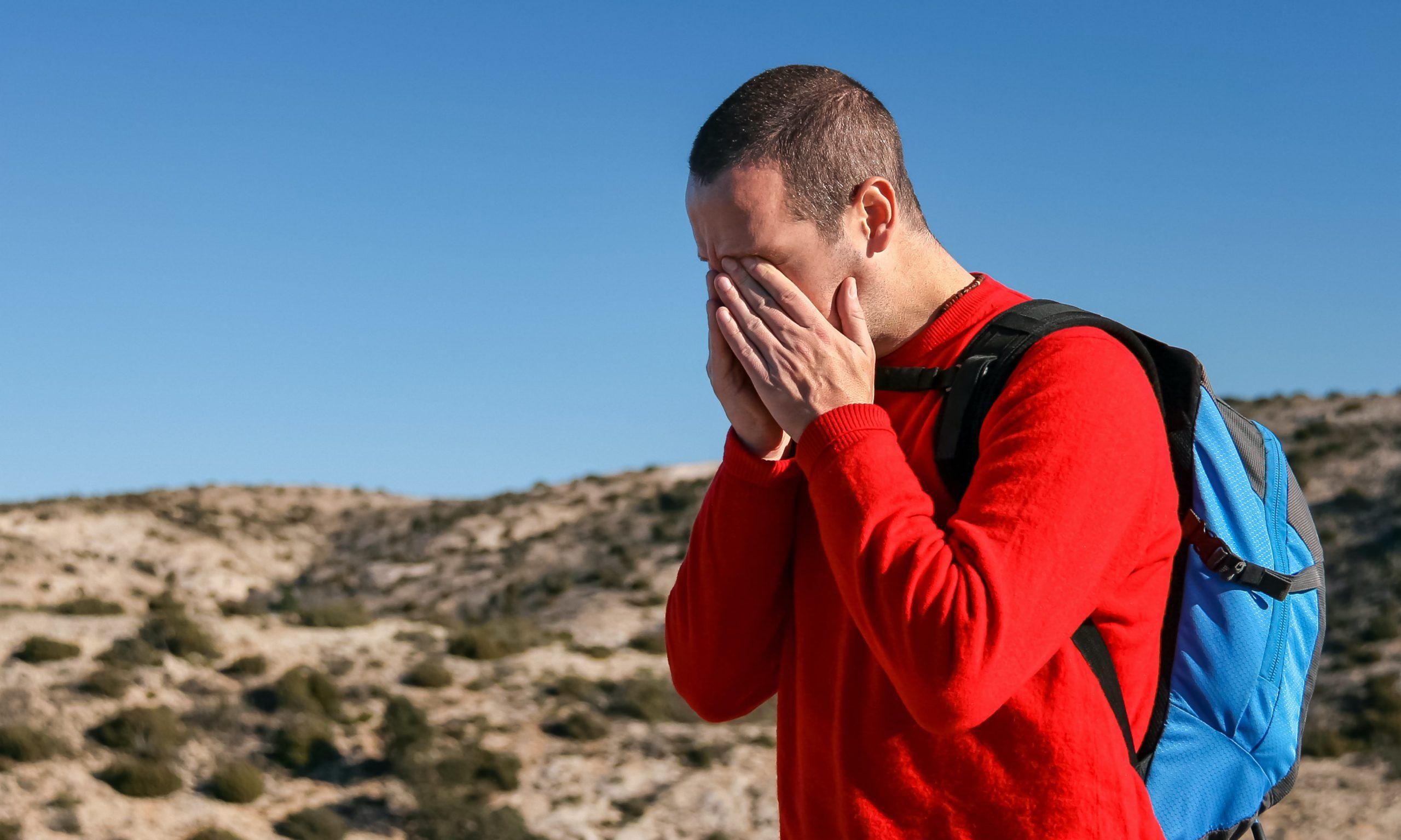 Man hiking in a red shirt having a headache