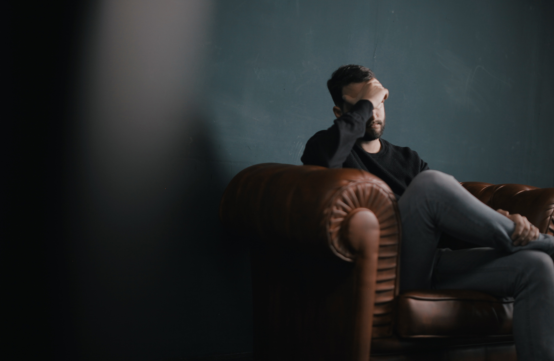 Stressed man sitting on the leather couch. Can Stress Cause Tinnitus?